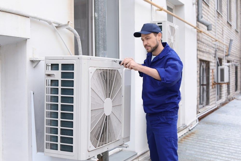 technician-in-bluesuit-checking-outdoor-ac-unit