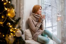 woman-holding-cup-wathing-from-window-near-christmas-tree